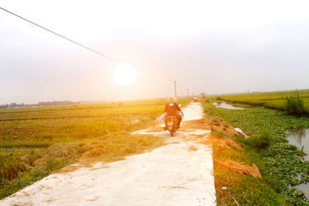 HAI DUONG, VIETNAM, AUGUST, 20: Asian woman riding a bicycle on the road on August, 20, 2014 in Hai Duong, Vietnam.