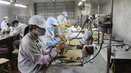 incus: HAI DUONG, VIETNAM, August, 3: workers castigate bronze casting products on August, 3, 2014 in Hai Duong, Vietnam. Editorial