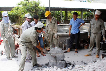 incus: HAI DUONG, VIETNAM, August, 3: workers removal mold bronze casting products on August, 3, 2014 in Hai Duong, Vietnam.