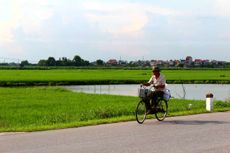 HAI DUONG, VIETNAM, AUGUST, 25: Asian man riding a bicycle on the road on August, 25, 2014 in Hai Duong, Vietnam