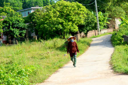 HAI DUONG, VIETNAM, AUGUST, 26: peasant woman with sickle on the road on August, 26, 2014 in Hai Duong, Vietnam.