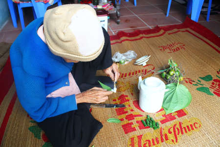 betel: Haiduong, Vietnam, December, 27, 2014: Woman making betel with betel and areca.  Customs of betel chewing is longstanding in Vietnam