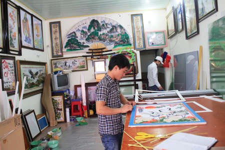 framer: Haiduong, Vietnam, February, 17: Craftsman working on frame in frame shop on February, 17, 2015 in Hai Duong, Vietnam