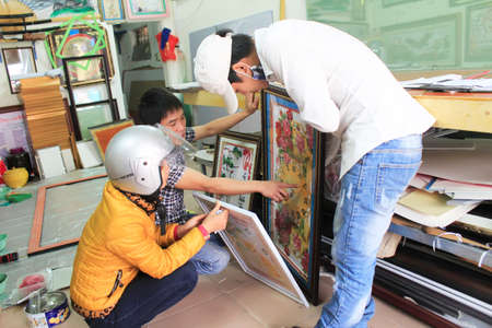 framer: Haiduong, Vietnam, February, 17: Craftsman working on frame in frame shop on February, 17, 2015 in Hai Duong, Vietnam