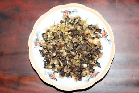 Closeup of eating the fried snails with stalks lemon grass Stockfoto