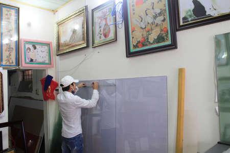 Haiduong Vietnam February 17: Craftsman working on frame in frame shop on February 17 2015 in Hai Duong Vietnam