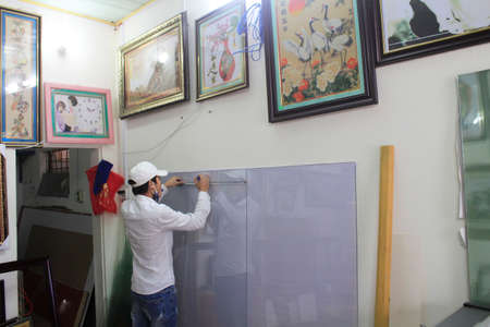 framer: Haiduong Vietnam February 17: Craftsman working on frame in frame shop on February 17 2015 in Hai Duong Vietnam