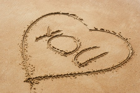 Heart shape symbol with the word you on sandy beach photo