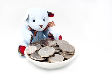 A blue teddy bear guarding Malaysia coins in a  plate with an isolated white background photo