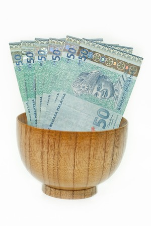 Malaysian Ringgit in a Wooden Bowl with an Isolated White Background Stock Photo