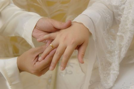 Mans Hand Putting a Wedding Ring on The Brides Finger  Stock Photo