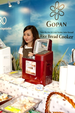 sanyo: KUALA LUMPUR - NOVEMBER 30 : Employee from Sanyo Electric showing Gopan a rice bread cooker during Malaysian Agriculture, Horticulture and Agrotourism Show (MAHA) on November 30, 2010 in Kuala Lumpur, Malaysia.