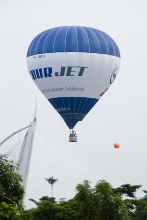 PUTRAJAYA, MALAYSIA - MARCH 19 : A hot air balloon from Switzerland in flight above the Wawasan Bridge at the 3rd Putrajaya International Hot Air Balloon Fiesta March 19, 2011 in Putrajaya, Malaysia.