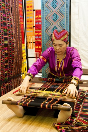 KUALA LUMPUR, MALAYSIA - MARCH 4: An unidentified woman, a traditional Li Brocade weaver from China does a demonstration at the Malaysia National Craft Day 2011 on March 4, 2011 in Kuala Lumpur, Malaysia Stock Photo - 9433980