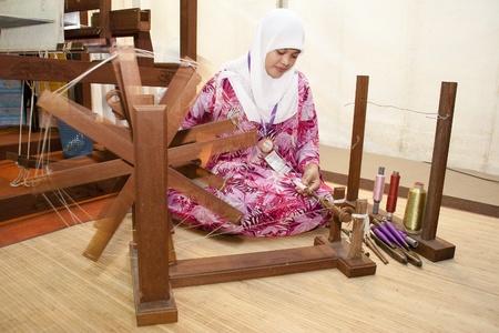 KUALA LUMPUR, MALAYSIA - MARCH 4: Norlianawati Ayob, a traditional Songket weaver prepare a yarn for the weaving process at the Malaysia National Craft Day 2011 on March 4, 2011 in Kuala Lumpur, Malaysia