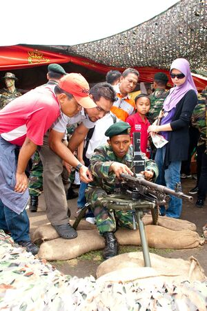 KUALA LUMPUR, MALAYSIA-MAR 5:Unidentified soldier brief visitor on weapon at the 78th Army Anniversary on Mar 5, 2011 in Kuala Lumpur, Malaysia. Malaysia spends 1.9 percent of its GDP on military.
