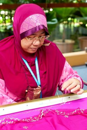 KUALA LUMPUR - MAY 28 : Robitah Hashim, a traditional Sulaman Kelingkam weaver does a demonstration at the Malaysia Wedding Craft Day 2011 on May 28, 2011 in Kuala Lumpur, Malaysia. Editorial