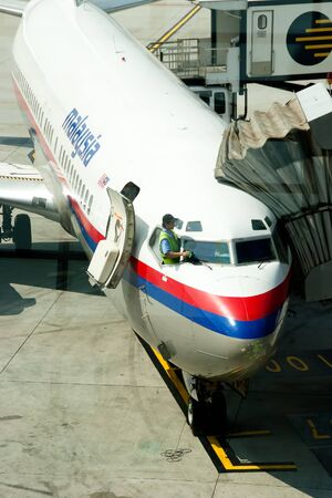KLIA-JUNE 25:An unidentified Malaysia Airlines employee prepares the plane for the next flight on JUNE 25 2011 in KLIA, Malaysia. Malaysia Airlines net profit  for Q3 2010 is at RM233 million ringgit Editorial
