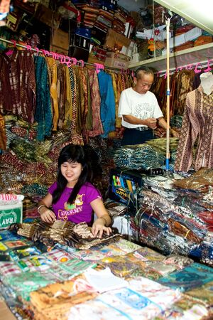 BANDUNG-JUNE 26:Unidentified batik sellers at Pasar Baru Trade Centre prepare for customer on June 26, 2011 in Bandung, Indonesia.In 2009 UNESCO recognized batik as an Indonesian cultural treasure.