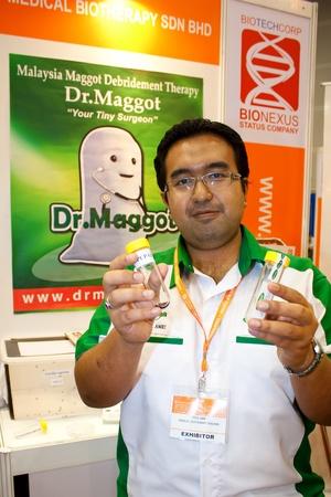 expositor: KUALA LUMPUR-NOV 22: Expositor celebraci�n de un tubo de Maggot Puppa a ser uso para la terapia larval en el desbridamiento BioMalaysia 2011 el 22 de noviembre de 2011 en Kuala Lumpur, Malasia.