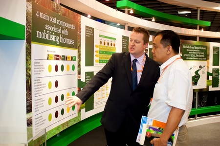 KUALA LUMPUR-NOV 22: Unidentified exhibitor explaining the Malaysia National Biomass Strategy to investor at the BioMalaysia 2011 Conference and Exhibition on November 22, 2011 in Kuala Lumpur, Malaysia.