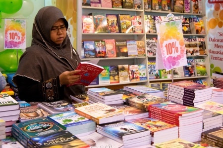 SHAH ALAM-Jul 3:Unidentified muslim visitor reading an islam religion book at the Selangor Book Fair on July 3, 2012 in Shah Alam, Malaysia. According to literacy statistics, Malaysians read about 8 to 12 books annually Editorial