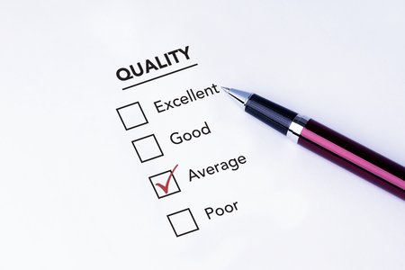 pen quality: Tick placed in average check box on quality service satisfaction survey form with a pen on isolated white background. Business concept survey.