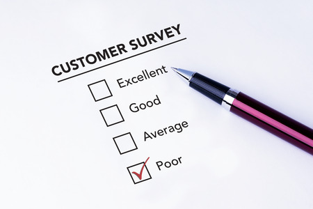 poor: Tick placed in poor check box on customer service satisfaction survey form with a pen on isolated white background. Business concept survey.
