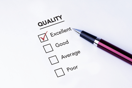 pen quality: Tick placed in excellent check box on quality service satisfaction survey form with a pen on isolated white background. Business concept survey.