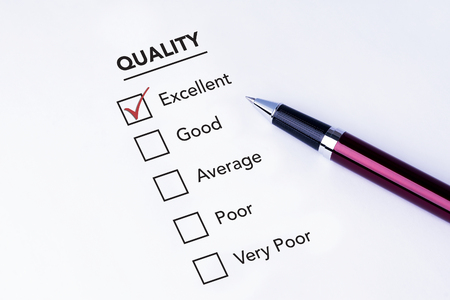 pen quality: Tick placed in excellent checkbox on quality service satisfaction survey form with a pen on isolated white background. Business concept survey. Stock Photo