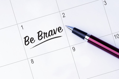The words Be Brave on a calendar planner to remind you an important appointment with a pen on isolated white background. New Year concepts of goal and objective.