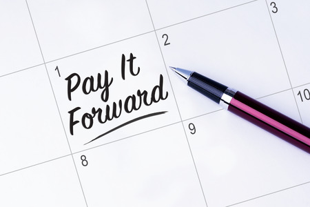 The words Pay It Forward written on a calendar planner to remind you an important appointment with a pen on isolated white background. New Year concepts of goal and objective. Stock Photo - 53125130