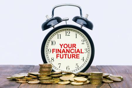 ingresos: palabra escrita su futuro financiero en un reloj con monedas de oro en la parte superior de una mesa de madera. Foto de archivo