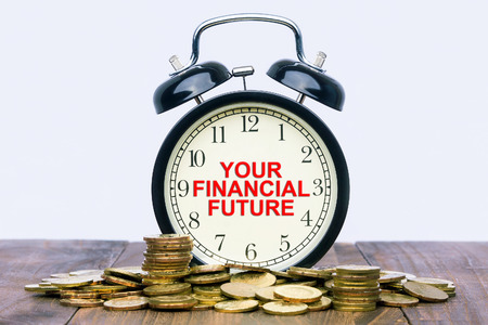 taxes budgeting: Written word Your Financial Future on a clock with gold coins on top of a wooden table.