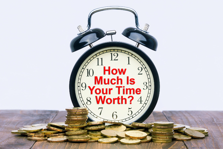 Written word How much is your time worth on a clock with gold coins on top of a wooden table.