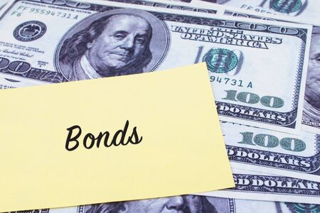 bonds: Focus on the words Bonds written on a yellow paper with USD dollars currency as a background. Concepts of investment and business. Stock Photo