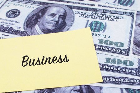 paper currency: Focus on the words Business written on a yellow paper with USD dollars currency as a background. Concepts of investment and business.