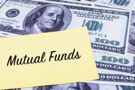 mutual: Focus on the words Mutual Funds written on a yellow paper with USD dollars currency as a background. Concepts of investment and business.