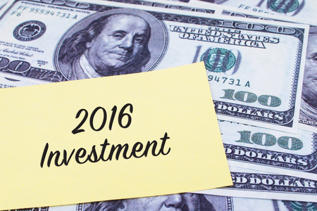 paper currency: Focus on the words 2016 Investment written on a yellow paper with USD dollars currency as a background. Concepts of investment and business. Stock Photo