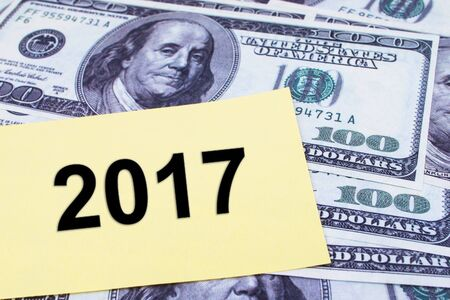 paper currency: The words 2017 written on a yellow paper with USD dollars currency as a background. Yearly Financial and Business Concept.