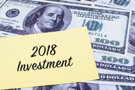 paper currency: Focus on the words 2018 Investment written on a yellow paper with USD dollars currency as a background. Concepts of investment and business.