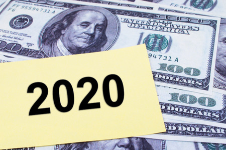 paper currency: The words 2020 written on a yellow paper with USD dollars currency as a background. Yearly Financial and Business Concept. Stock Photo