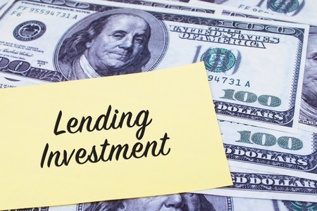 lending: Focus on the words Lending Investment written on a yellow paper with USD dollars currency as a background. Concepts of investment and business.