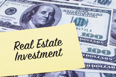 Focus on the words Real Estate Investment written on a yellow paper with USD dollars currency as a background. Concepts of investment and business.
