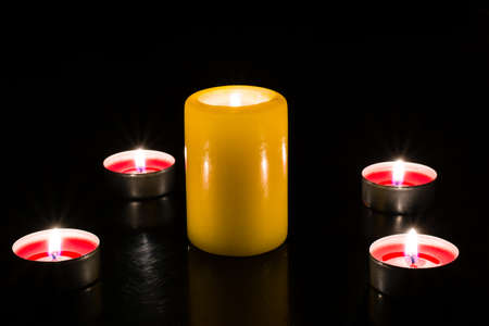 suppository: A large candle surrounded by small candles on a dark background in the light of the flame