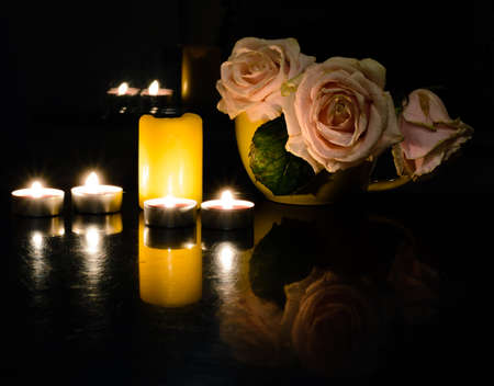 suppository: An arrangement of scented candles on the table in the evening for dinner and flowers. Romantic dinner for Valentines day.