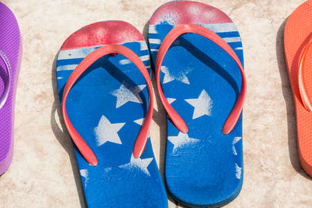 flip flops: Women flip flops colors of the American flag lying on the floor covered with tile