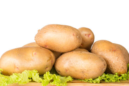 spud: Raw potatoes lies on a chopping Board surrounded by greenery on a white background