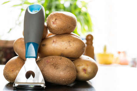 spud: A lot of raw potatoes lying on the table near the window. Still life of potatoes. Stock Photo