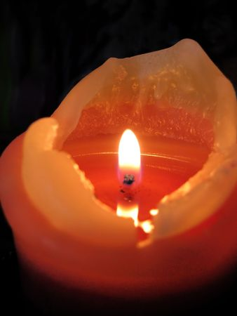 Burning candle on a black background. Vertical photo